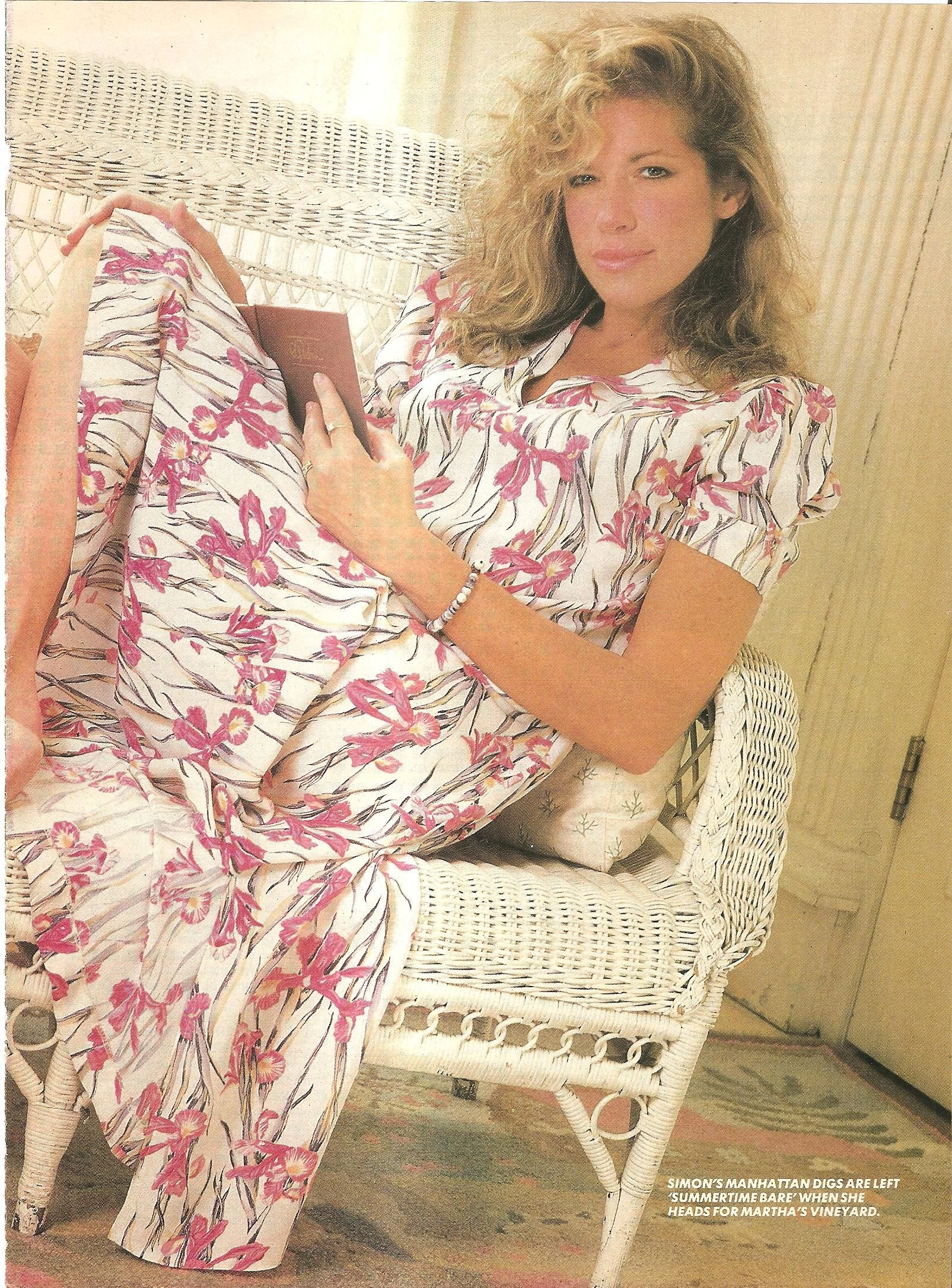 Carly Simon sitting in wicker, wearing a dress, reading a book in photo from US magazine Aug 26 1985