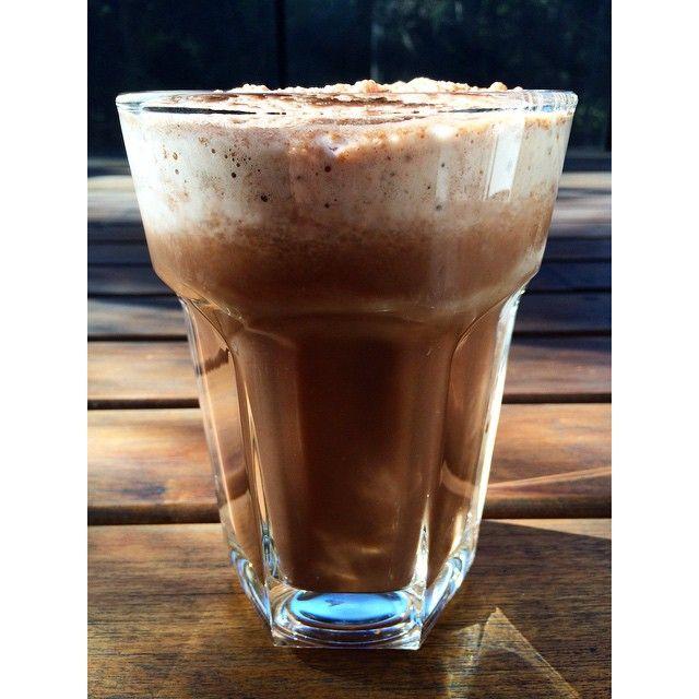 Pone en la licuadora mucho hielo + bastante agua helada + un chorro de leche (yo le pongo apenas para que no sea tan pesado) + 1/2 banana + 1 cda grande de cacao amargo + endulzante!