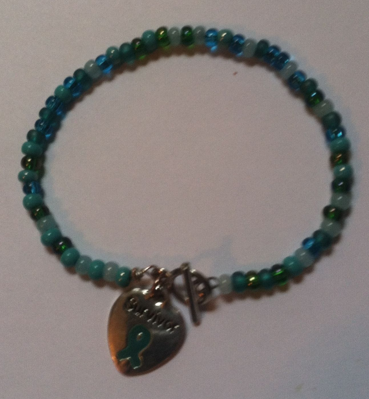 Simple Survivor Bracelet  7 1/2 inch bracelet made with glass beads and a silver toggle clasp with a heart shaped survivor charm.  $12.99