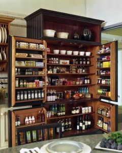 A hardwood built-in Chef's pantry with double doors. Interior shelves and racks hold bottled goods, while the shelves behind the swinging doors are for lighter items like salt, pepper, and other condiments. The uncovered shelf up near the ceiling serves to display ornamental jars and bowls.