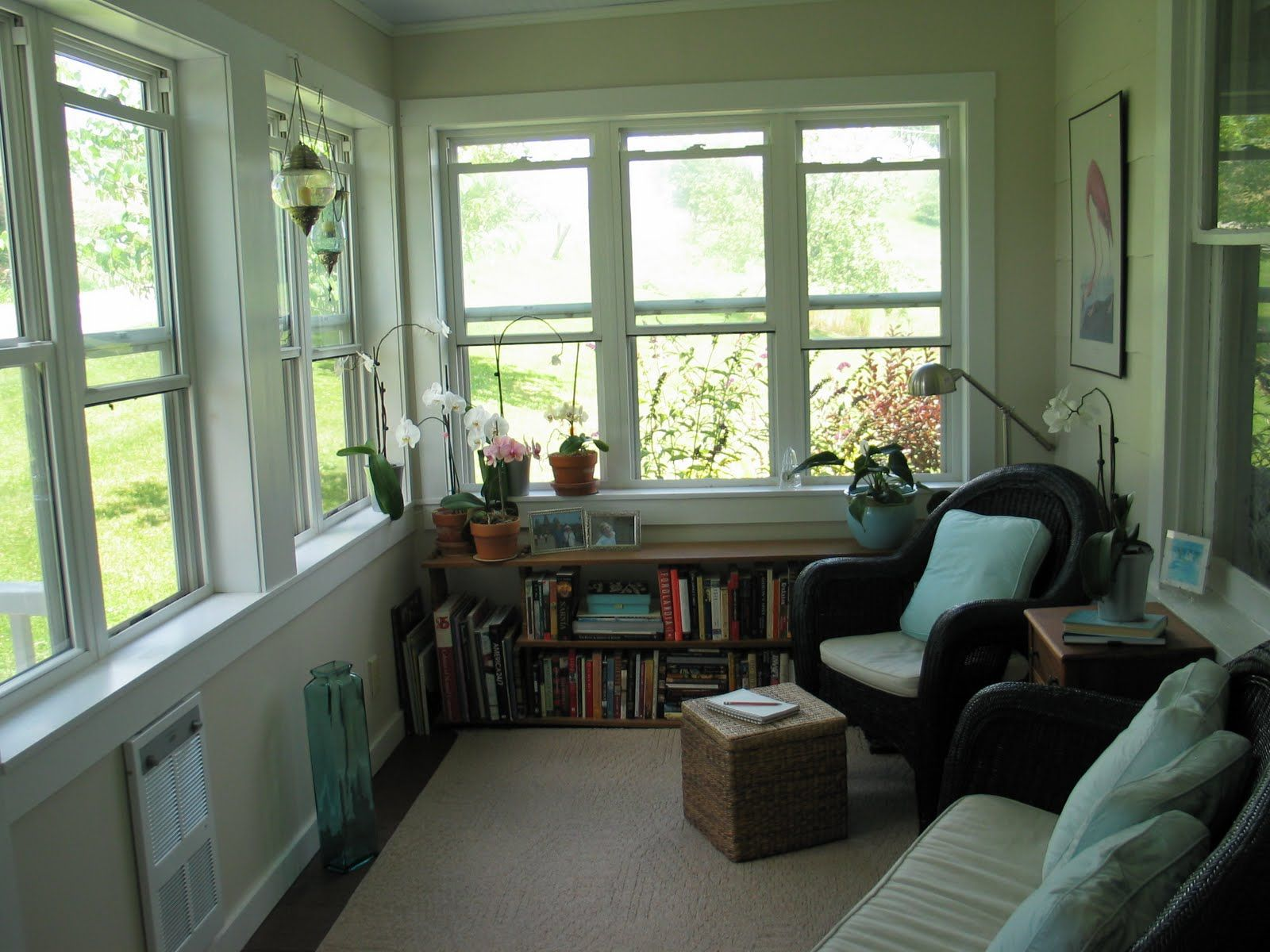 Sun room stunning white wall painted with low bookcase for Enclosed porch furniture ideas