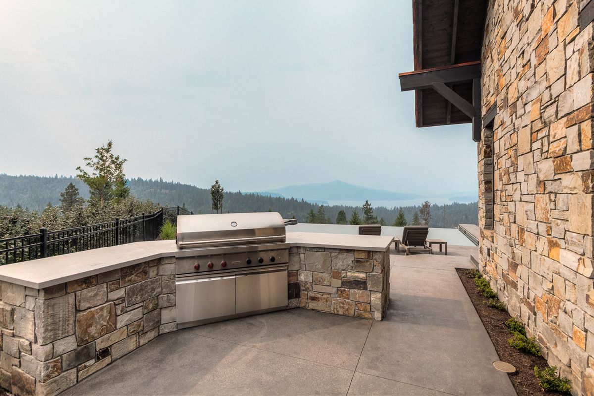 Custom Stone Wrapped Built In Barbecue On Concrete Patio With Negative Edge Pool In Background Custom Homes Custom Home Builders Home Builders