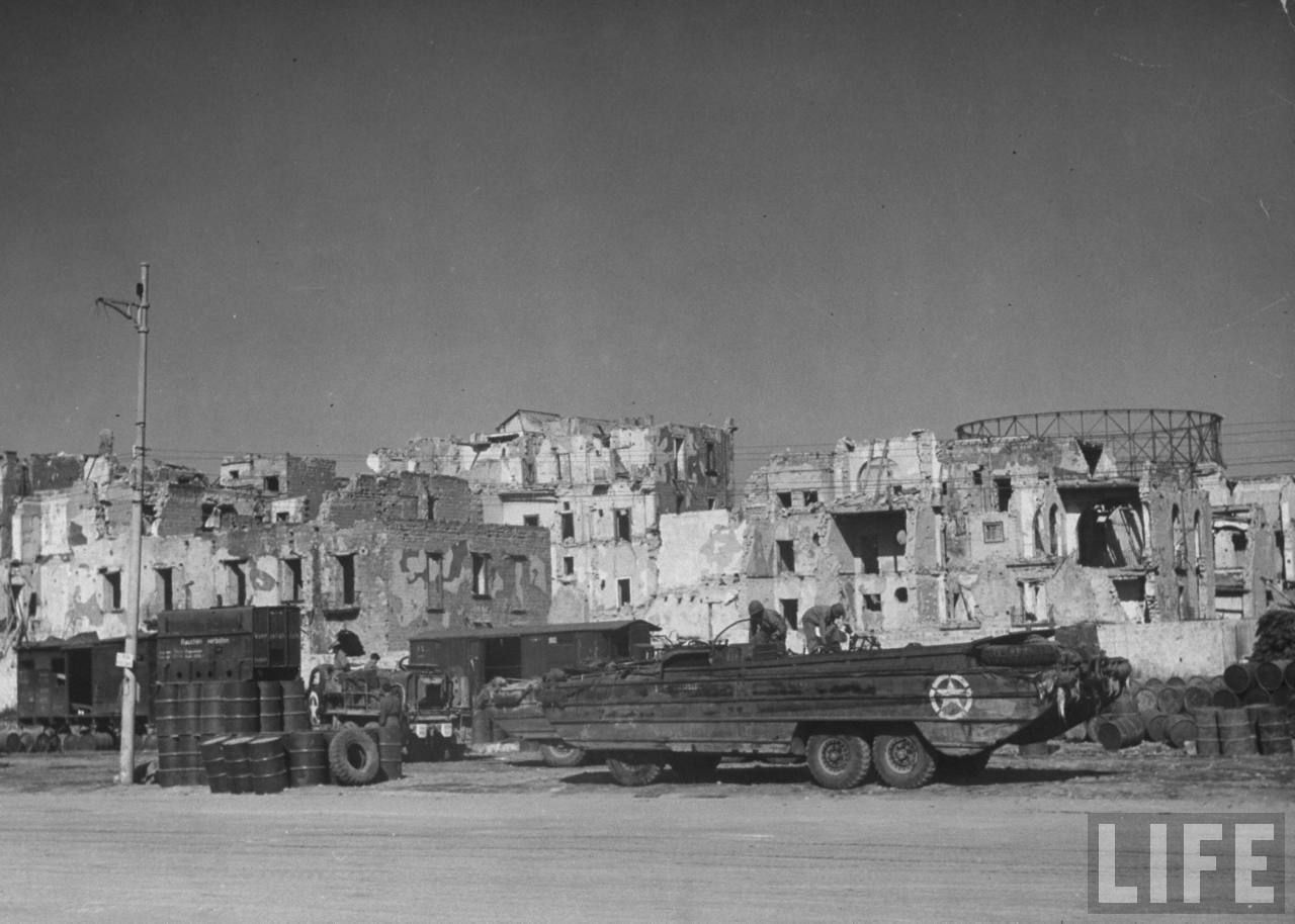 US Army In Naples October 1943 American soldiers working on amphibious vehicle in front of bombed-out buildings, during cleanup of damage done by evacuating German demolition teams. Photo by Margaret Bourke-White courtesy of Life Magazine Posted by Charles McCain