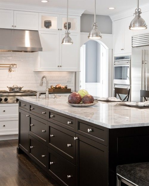 Black island with marble counter, white perimeter cabinets with dark counters, white subway tile? on walls, pendants, wood floors? The Fat Hydrangea: Kitchen