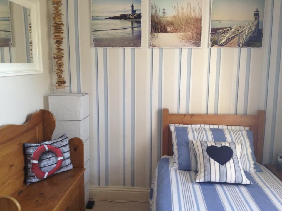 Beach themed bedroom Laura Ashley wallpaper (Seaspray) and pale twine paint.