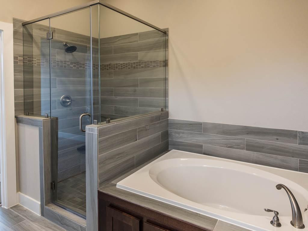 The master bath features a large soak tub and separate for Master bathroom glass doors