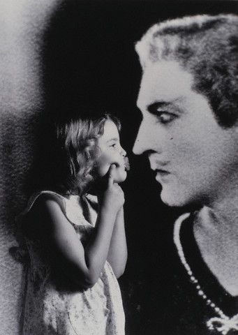 Lttle Drew Barrymore and a photograph of her grandfather John Barrymore