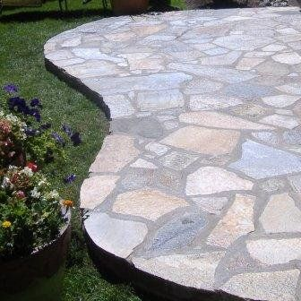 Awesome A Raised Flagstone Patio Spills Out Over A Lush Green Lawn.