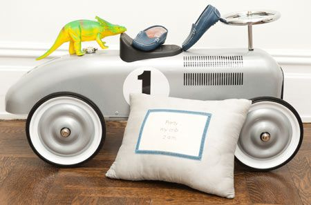 Silver vintage race car beautifully shot with sentimental needlepoint pillow, baby shoes and toy.
