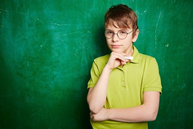 Niño pensativo con gafas y una tiza Foto Gratis