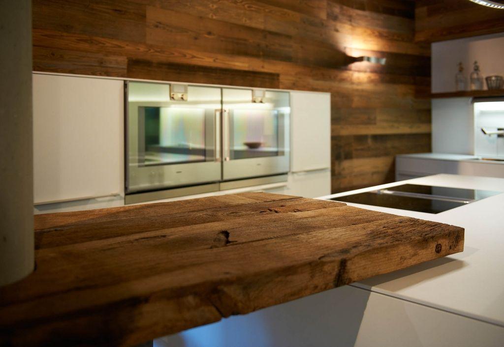 Glatte Weiße Arbeitsflächen Treffen Auf Rustikales Altholz In Moderner Küche
