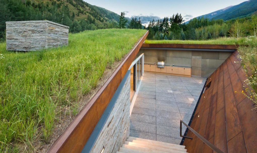 A white oak rain screen clads the exterior of the bedroom wing, while a sunken courtyard to the west features a fireplace built into the Corten steel retaining walls.
