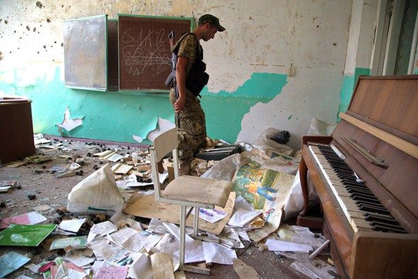 An Ukrainian serviceman patrols in a school destroyed after a shelling between Ukrainian forces and pro-Russian separatists in Pisky village, Donetsk region on June 10, 2015. This frontline Ukrainian village lacks gas, power and water. Yet with barely a house left standing, Pisky remains a daily target of shelling, despite the latest truce with pro-Russian rebels, and Kiev's troops are digging down to survive. AFP PHOTO / OLEKSANDR RATUSHNIAK