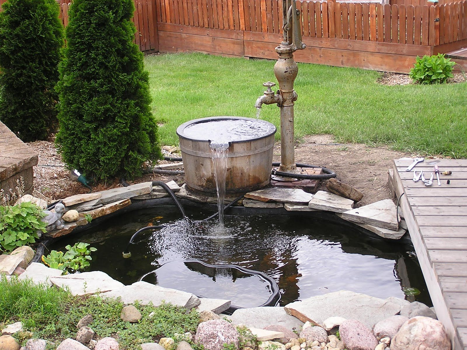 Landscaping around a water feature antique water pump for Fish pond fountain design