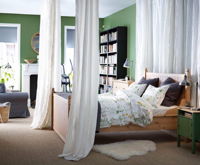 Slaapkamer met houten bed gebloemd beddengoed witte gordijnen