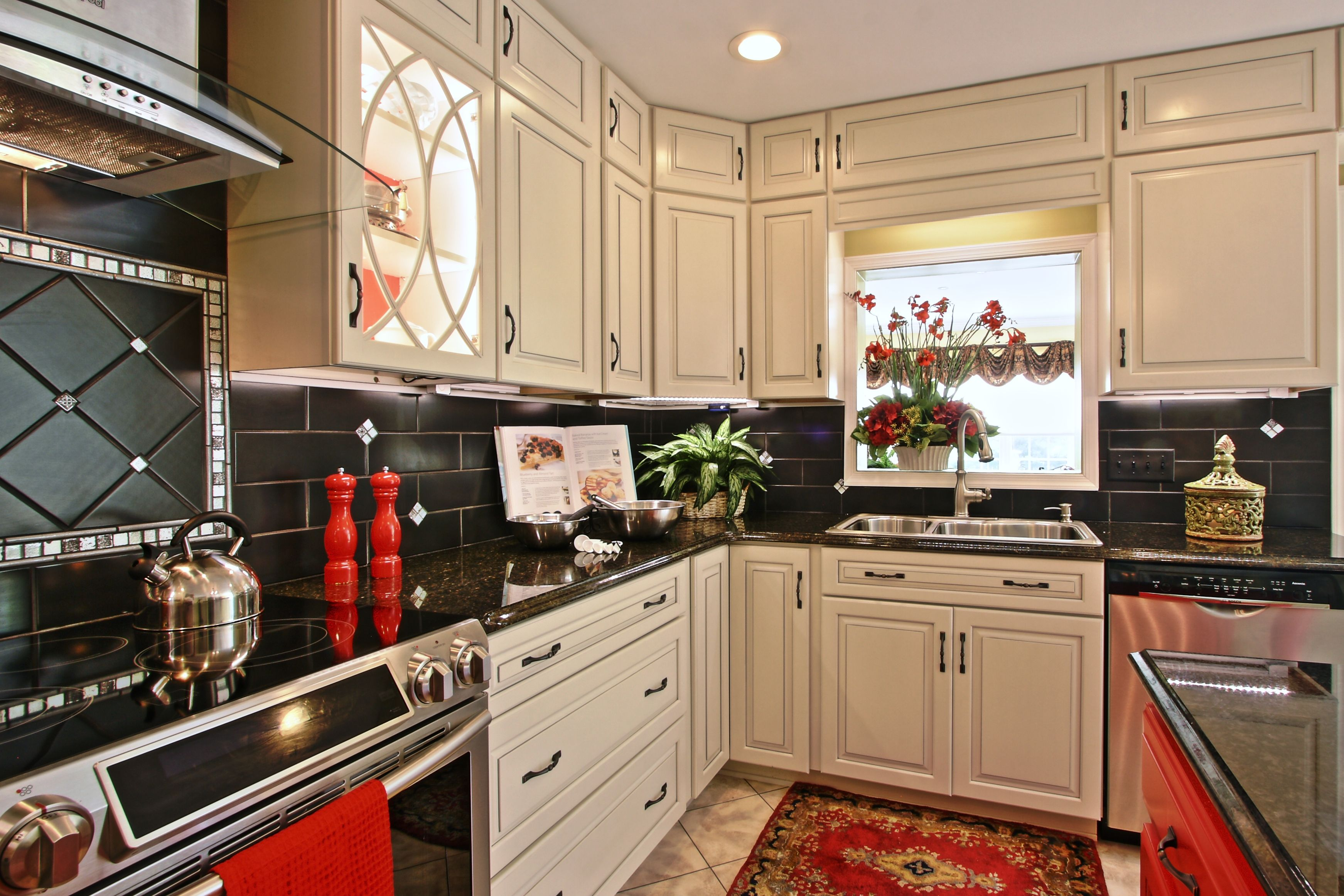 Red, black and white kitchen. Glass door cabinets with ...