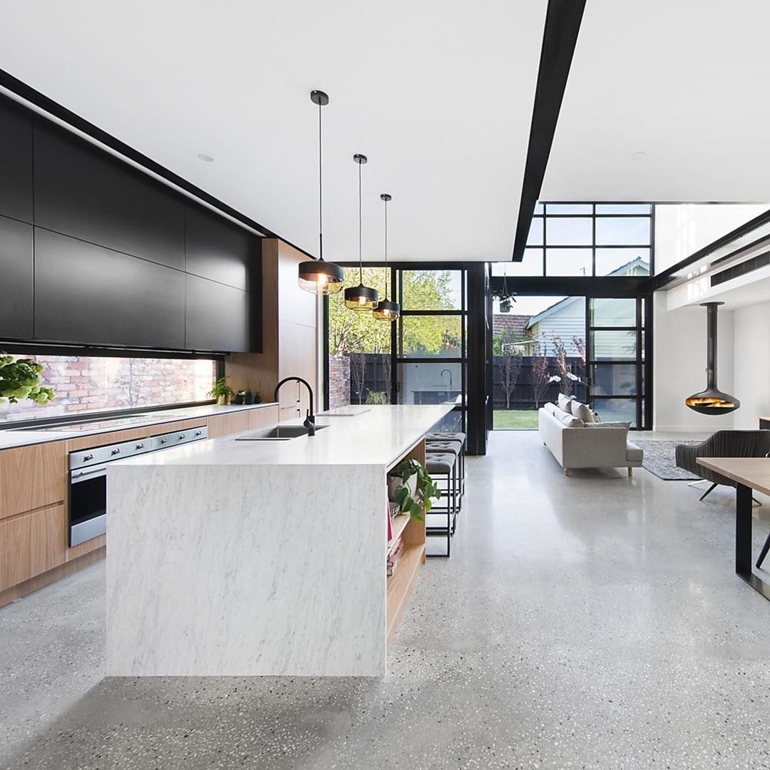 Grey polished concrete floor with black and white aggregate black framed windows black and wood kitchen cabinets window splashback