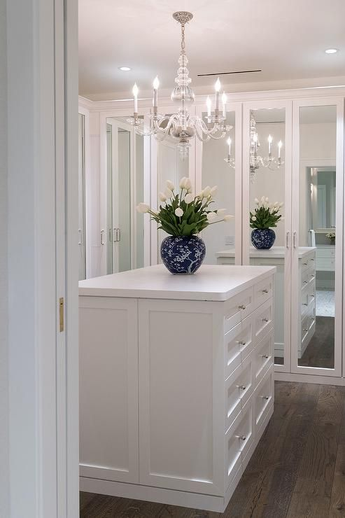 A George Ii Chandelier Hangs Over A White Closet Island Fitted With Jewelry Drawers And Topped With A Blue Vase In 2020 Closet Island Closet Decor Wardrobe Room