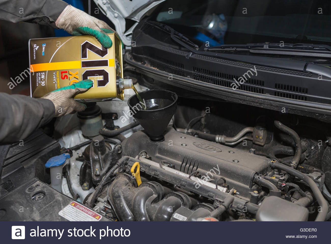 Download this stock image Mechanic checking the oil level
