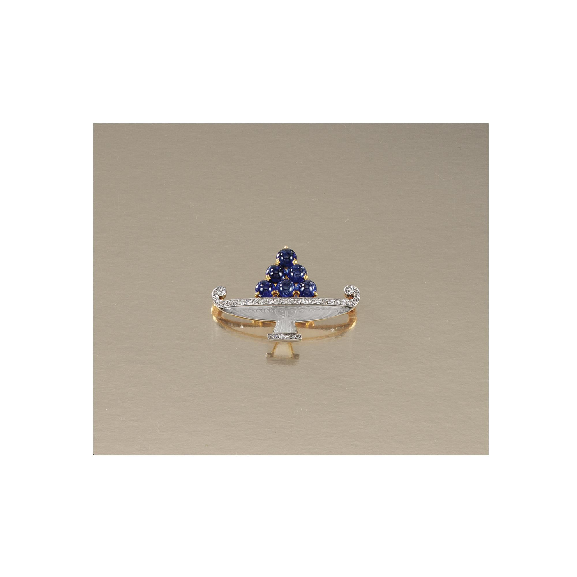 "ROCK CRYSTAL, SAPPHIRE AND DIAMOND ""FRUIT BOWL"" BROOCH, CARTIER, CIRCA 1915 Designed by Charles Jacqueau, the carved rock crystal fruit bowl lined with millegrain-set circular-cut diamonds and embellished with fruit of sapphire beads, signed Cartier, French assay marks.  Estimate   2,960 - 3,946USD  LOT SOLD. 11,839 USD"