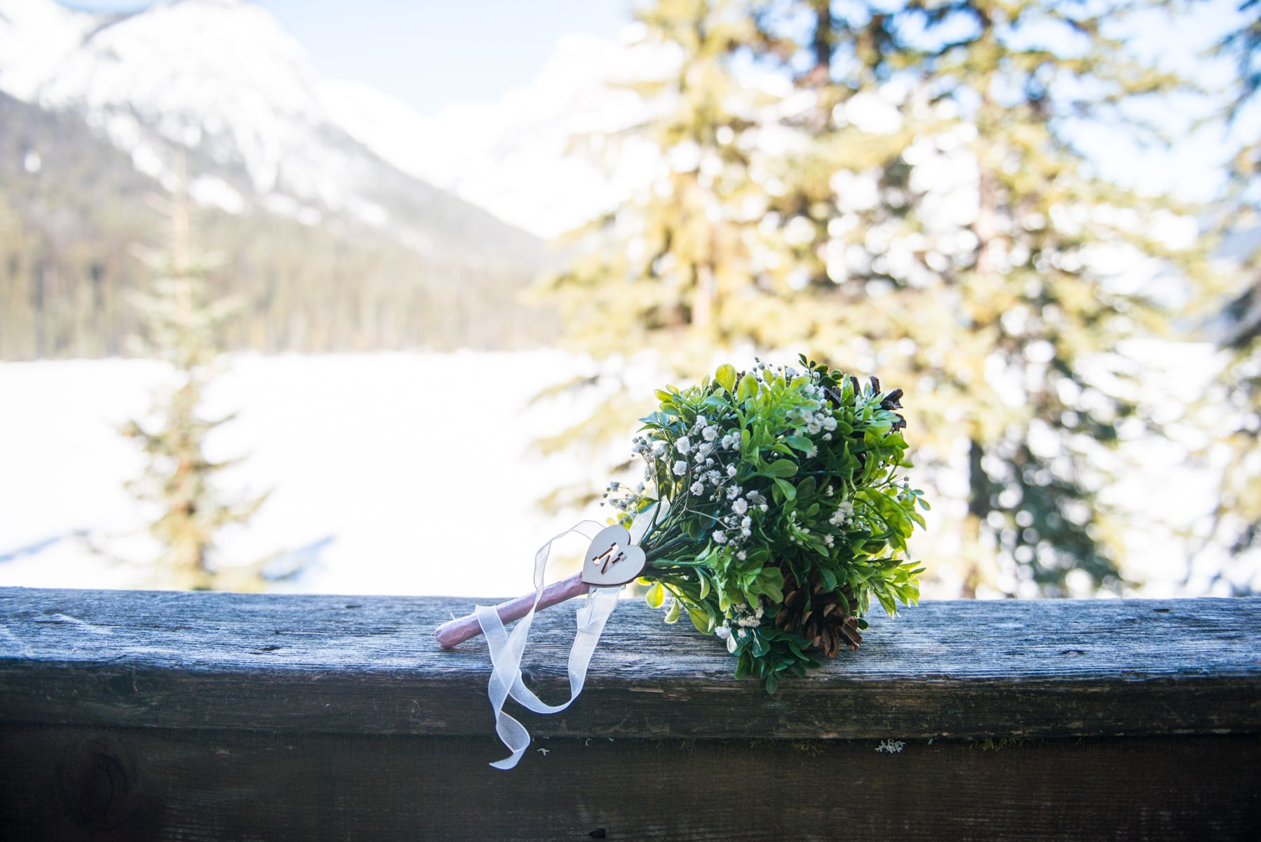 Natural green and white bride's wedding bouquet in front of beautiful Emerald Lake, Canadian Rockies. Photo by one-edition.ca.