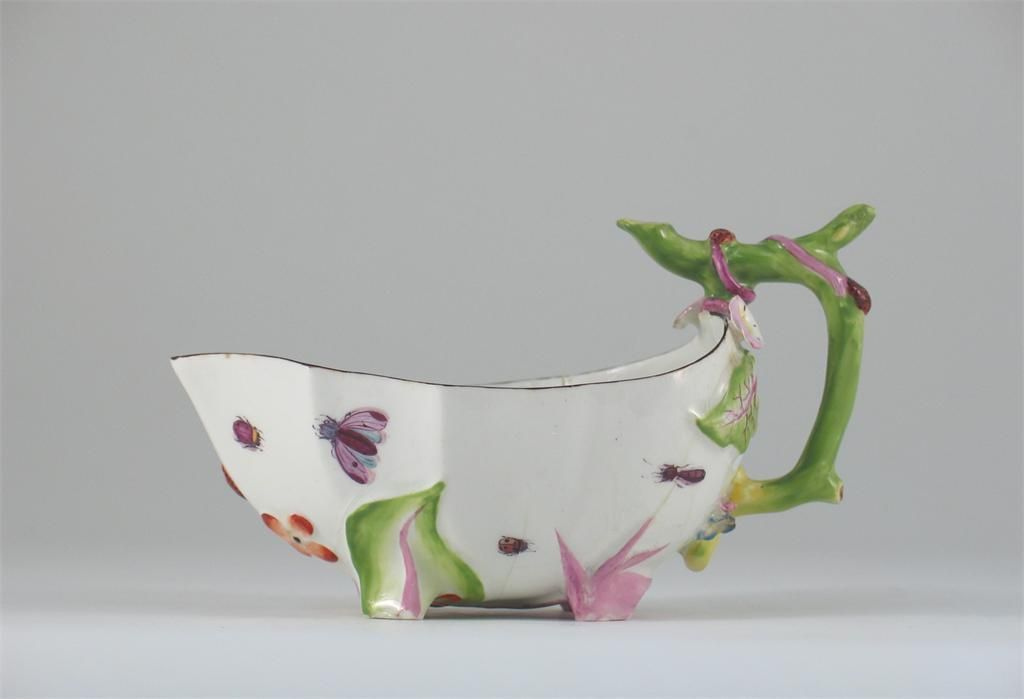 A botanical Chelsea sauceboat, with a stalk handle and four moulded feet, the interior painted with a large green leaf, and blue bell flowers, the exterior with bugs and strawberries, red anchor mark. c.1755, 16.5cm.