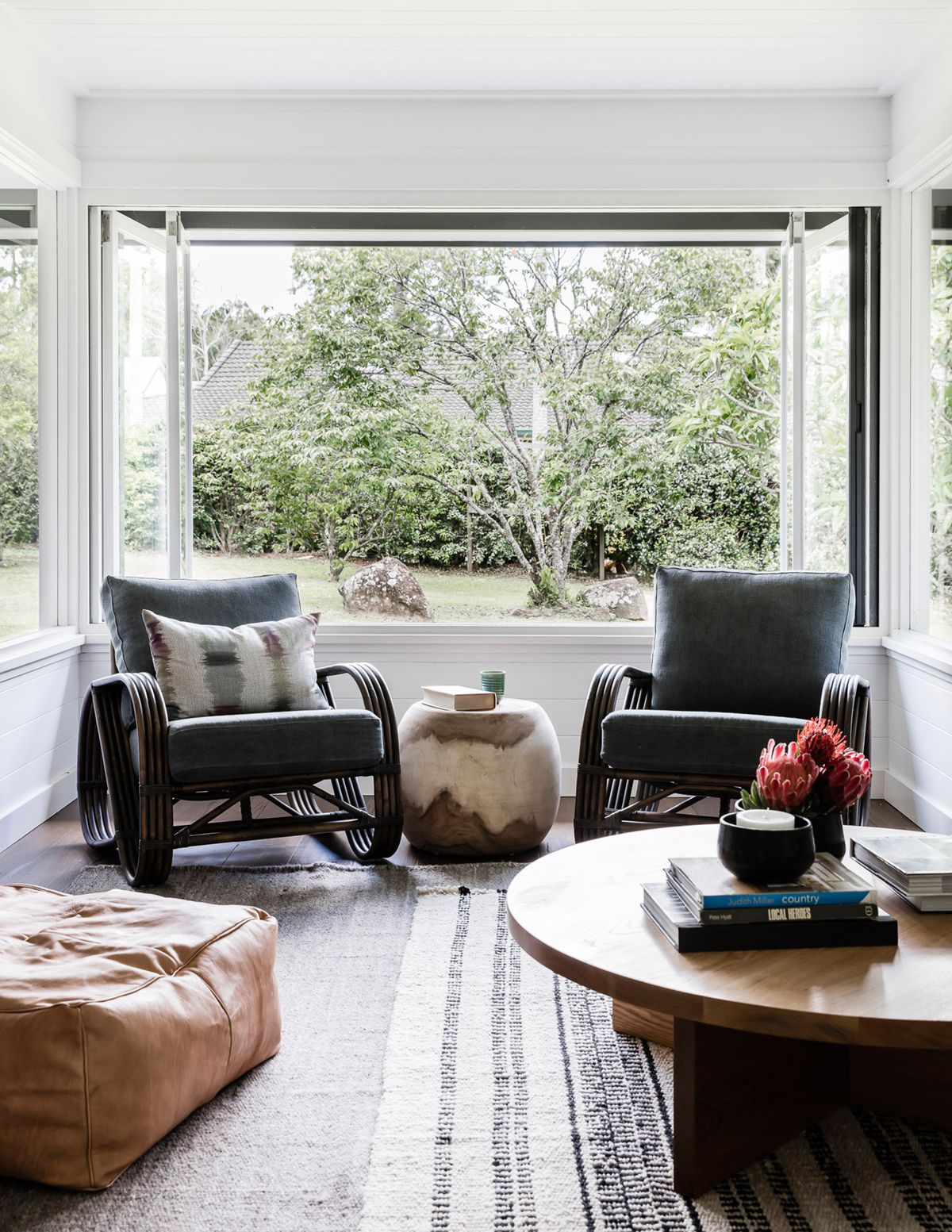 Dark bamboo lounge chairs and layered rugs earthy modern bungalow house tour on coco kelley