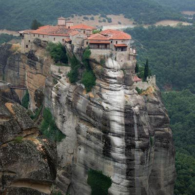 "Meteora Monasteries. Kalambaka, Greece. These are real, inhabited buildings built right up to the edge of a nearly 1,000 foot cliff drop. The strange Greek mountain formations of the Meteora (Greek for ""in midair"") have been home to monks since at least the 11th century. Numerous monasteries cropped up throughout the rocks over the subsequent centuries, six of which are still in use and open to the public—assuming, of course, that the public has the fortitude to make the climb."