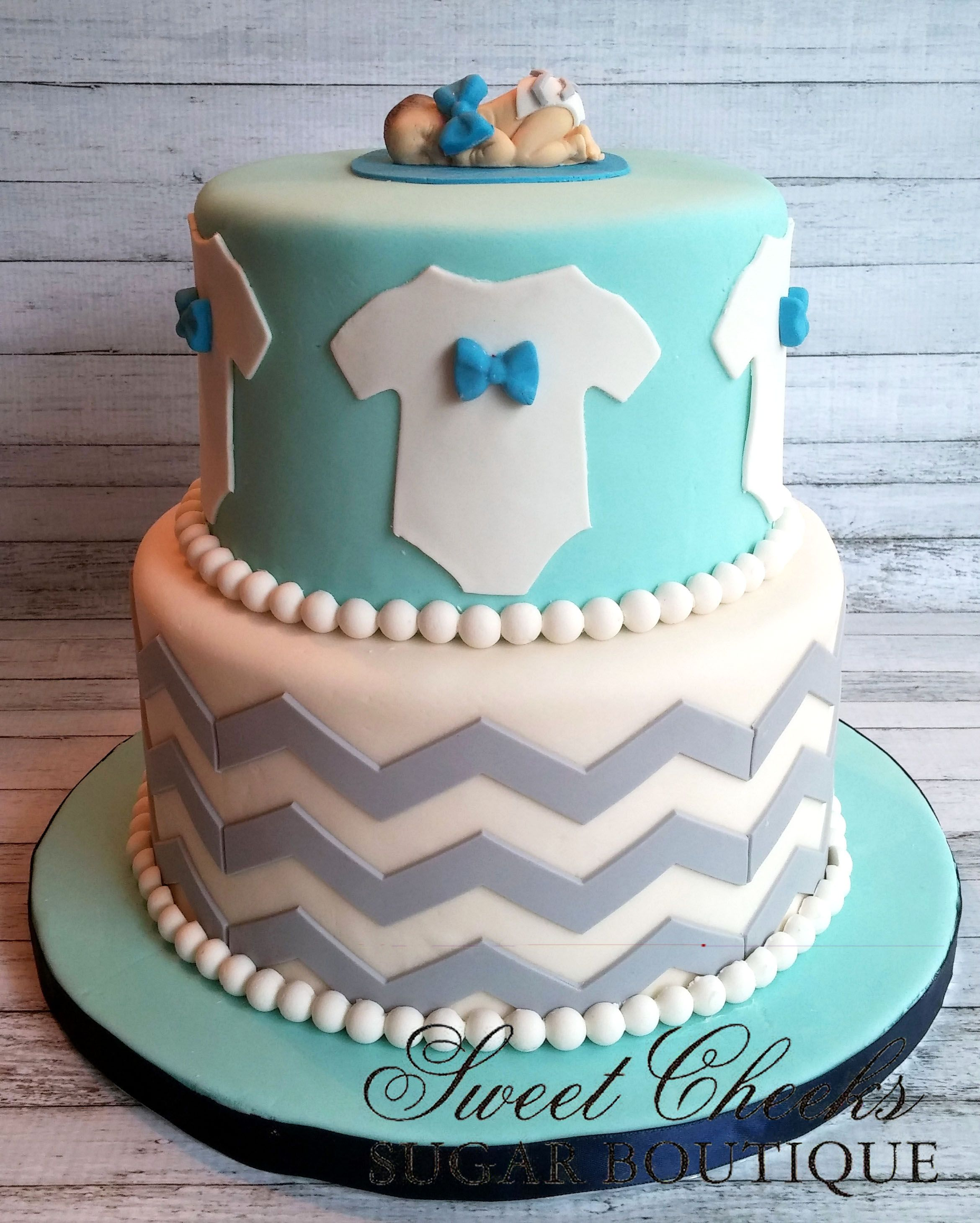 A bow tie and chevron baby shower cake to wel e a sweet little