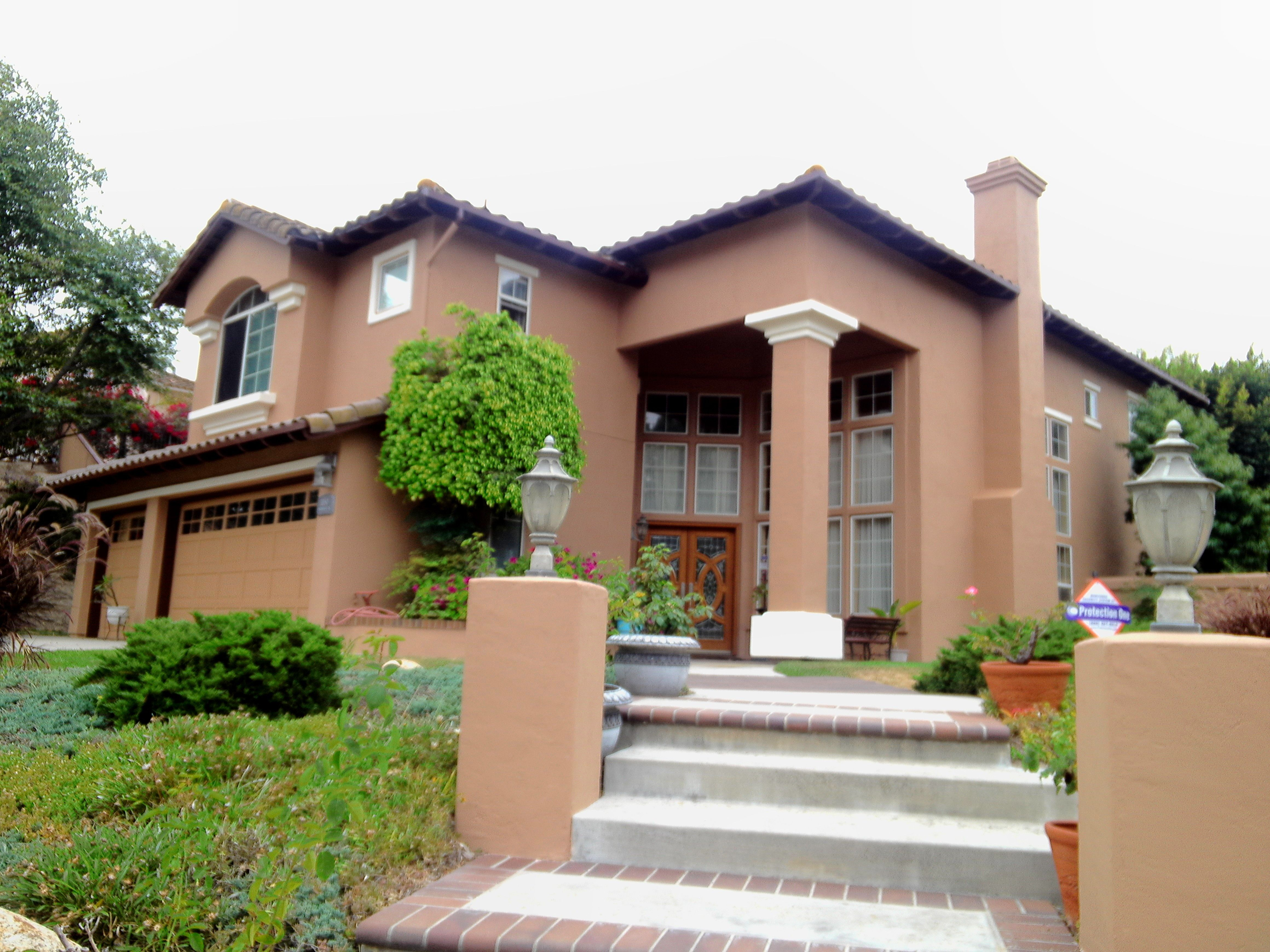 brown stucco house paint with cream pop outs and cedar wood stain
