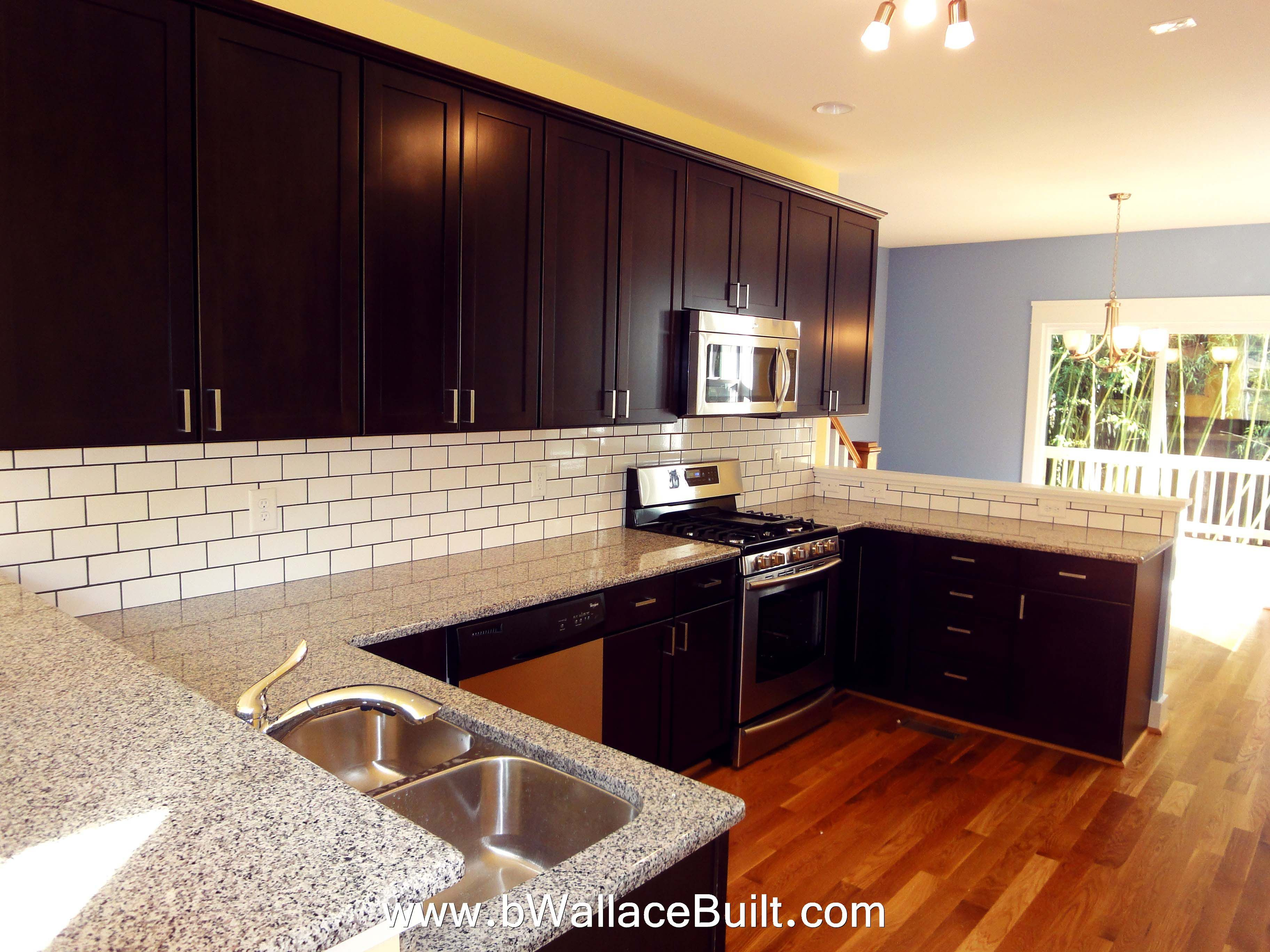Large open Kitchen w/ white subway tile backsplash and  a dark cabinet looks sophisticated.