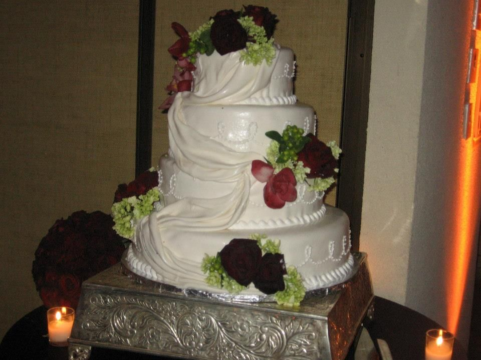3 tier wedding cake made of butter cream. has fresh flower placed all over the cake