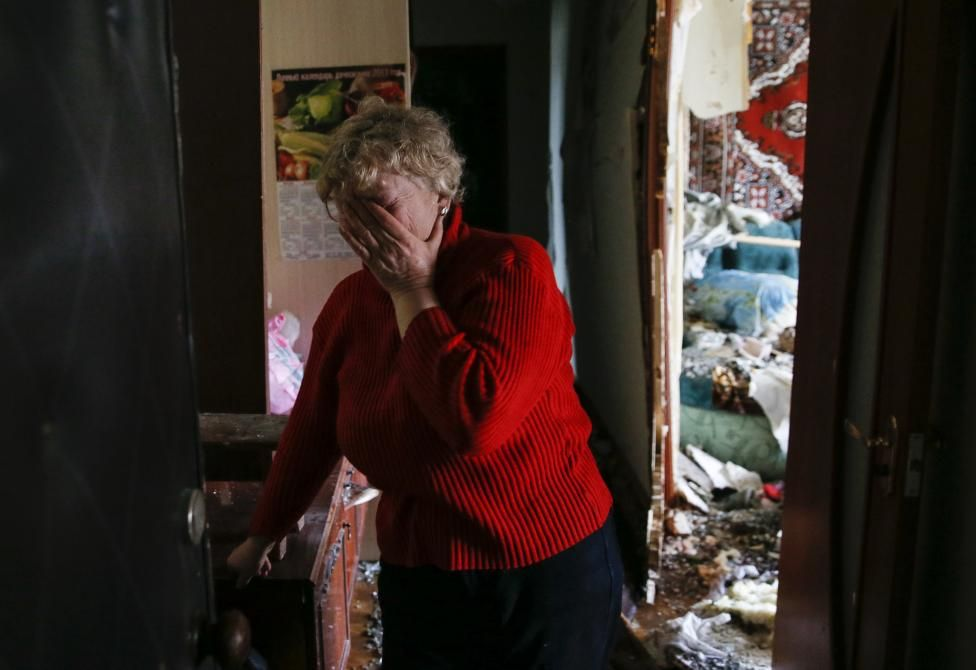 A woman reacts as she looks at the debris inside a flat at a residential block damaged by recent shelling in Yenakieve town, northeast from Donetsk, February 2, 2015. REUTERS/Maxim Shemetov