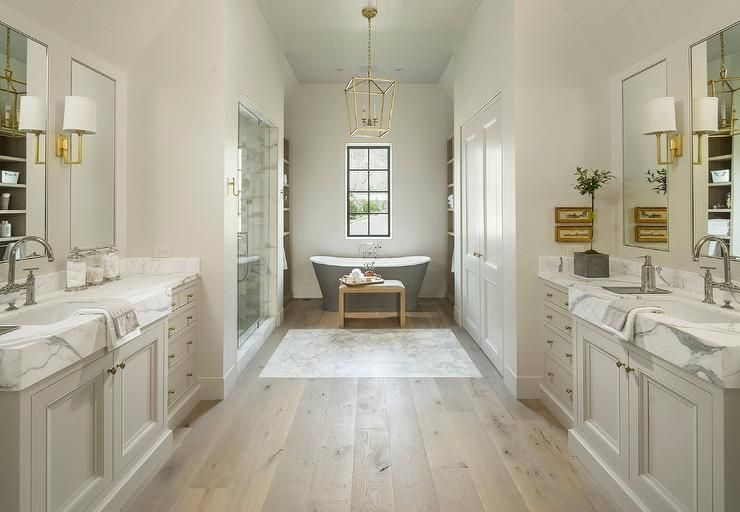 Well appointed gray master bathroom features facing pale gray washstands fitted with brass knobs and thick marble countertops holding a large sink with a large deck mount bridge gooseneck faucet fixed under a inset vanity mirrors lit by brass sconces.