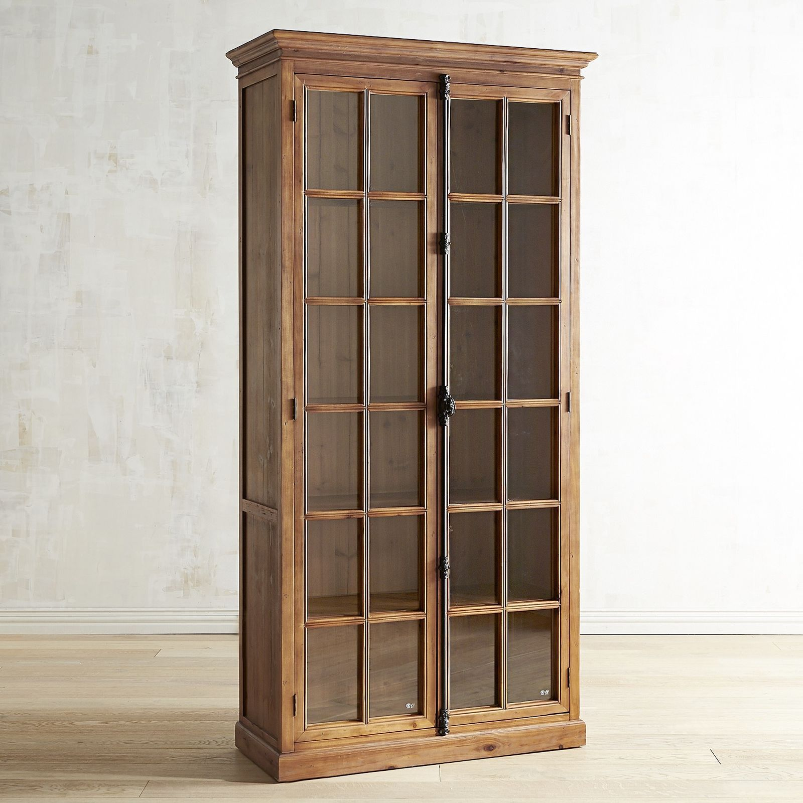 """Originating in 19th century Europe, the """"Cremone bolt"""" is a traditional casement-window locking device with a latch/handle mechanism. Featured on all our hand-hewn Cremone cabinetry, it's as beautiful as it is functional. Also featured: Brown wood frames with protracted crown molding, contrasting natural wood casements and tempered pane-glass windows. Over 8' tall, our cabinet houses five adjustable shelves."""