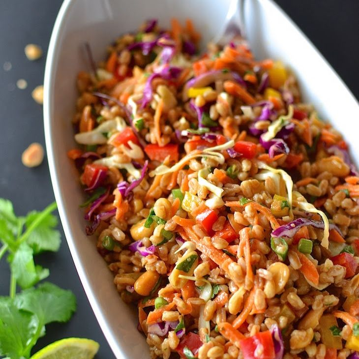 Rainbow Thai Farro Salad Recipe Salads with peanut butter, honey, ginger, low sodium soy sauce, sesame oil, lime, rice vinegar, water, farro, red bell pepper, yellow bell pepper, carrots, shredded cabbage, cilantro, green onions, peanuts, lime wedges, peanuts