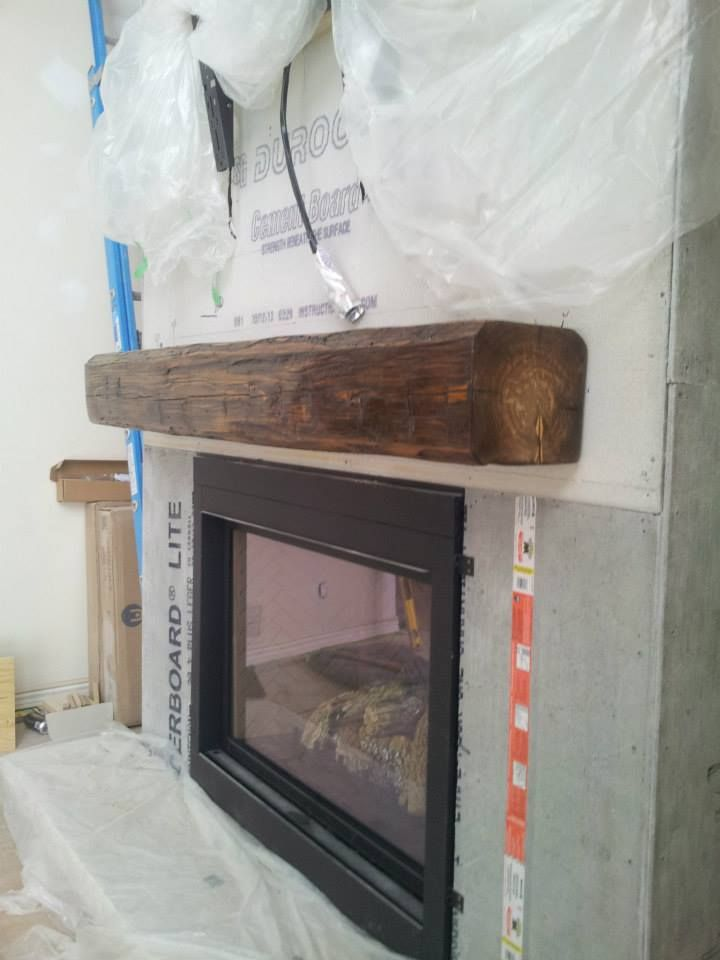 Installing a barn beam mantel BEFORE the stone is the best option. Here is one of our custom fireplace mantels installed before the stone is set.