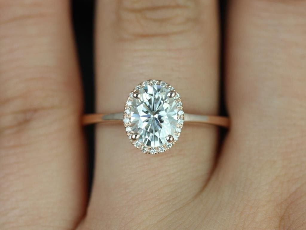A simple rose gold band Platinum head with an oval shaped center diamond and