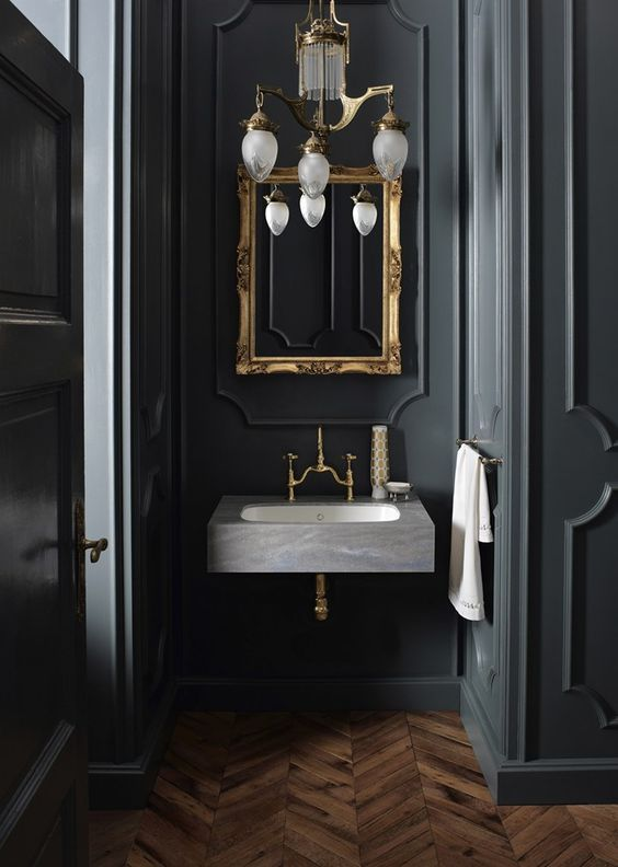Photo of A vintage chandelier, a mirror in a gold-colored frame and brass fittings …