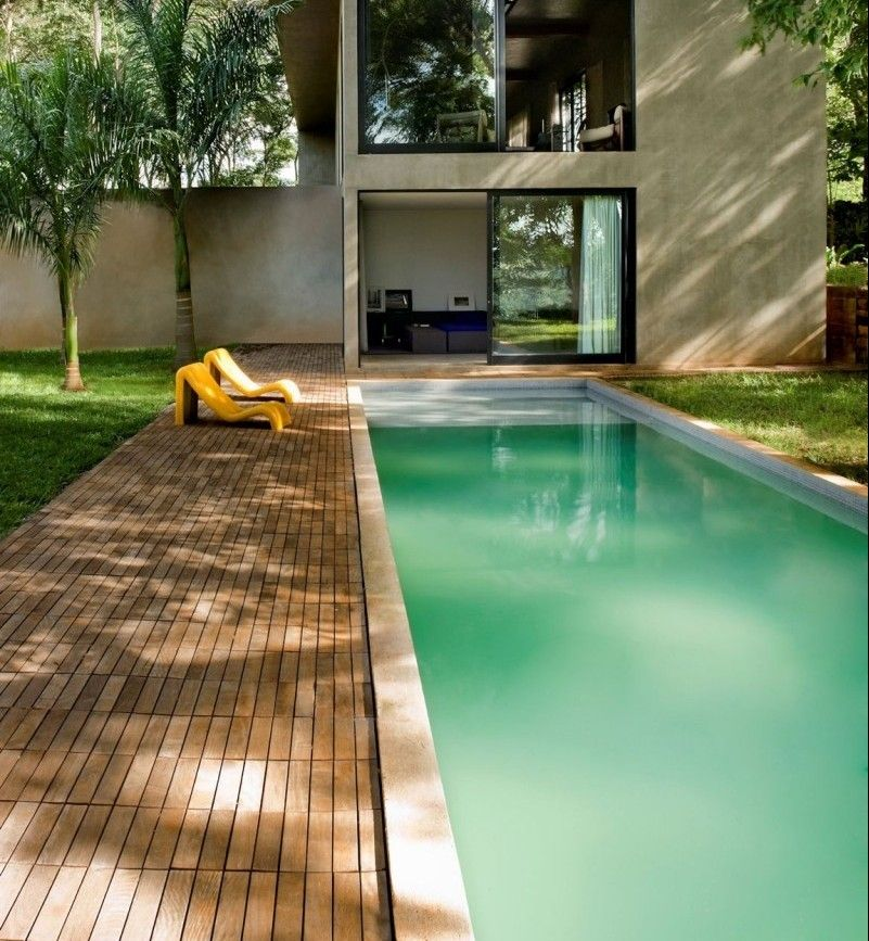 Holz Poolterrasse, grüner Pool und gelbe Sonnenluegen Garten