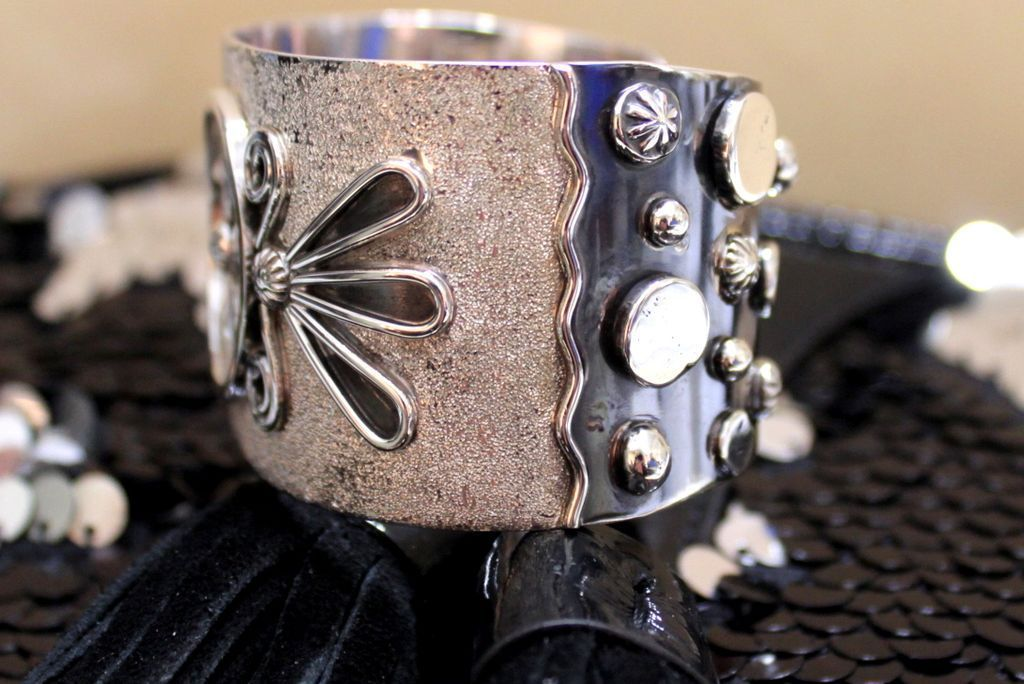 Sterling cuff, it has a tribal Petroglyh on the center of the cuff with a brushed spurred surface. the terminals are decorated with reflection pools, raindrops, stars and sunbursts. It has the Nakai Hallmark with Sterling.