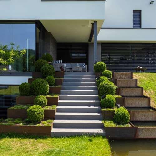 Minimalistische Gartengestaltung am Hang mit Wasserbecken aus Cortenstahl und Feuerstelle | Rheingrün #dekoeingangsbereichaussen