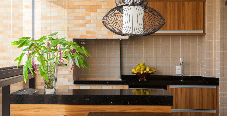 Esta varanda gourmet tem estilo rústico pelo uso da madeira, pastilhas, tijolinho e bancada em granito. Destaque para o pendente que dá um toque moderno  ao espaço. Projeto da arquiteta Eliana de Souza.