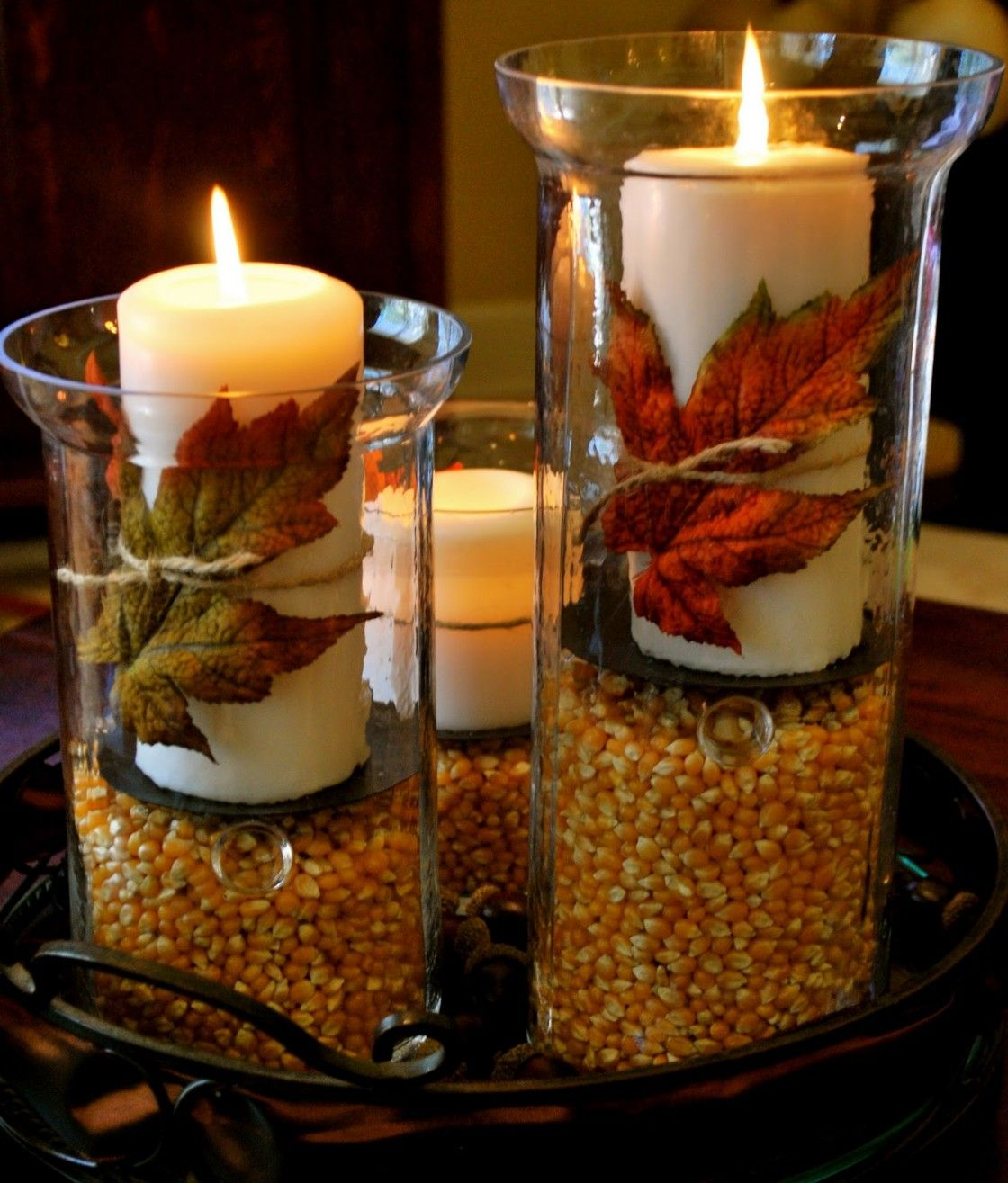 Tie an autumn leaf (real or faux) with raffia around candles, place on a holder on seed corn (or popcorn kernels - or acorns) in tube glass or hurricane vases - arrange assorted sizes on a tray for a centerpiece #herbstdekotischtablett