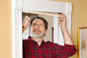 toh master carpenter Norm Abram reaching up to fix a sliding door rail in the doorway above his head