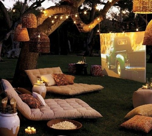 LOVE! It's like a drive in only better! The string lights and wicker basket hanging lights really warms the space with out distracting from the movie projector. Have your own movie premier night or even spend a night watching old home made videos!    Beautiful Backyards