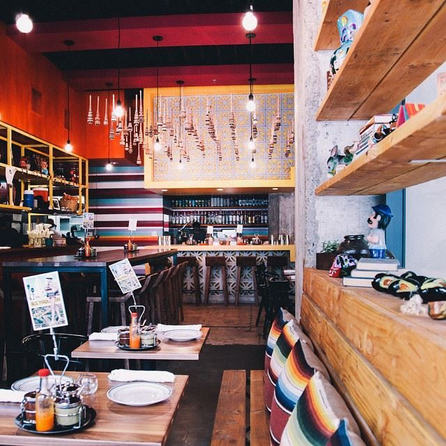 One more of @bstaqueria. A big theme in the branding (by @loveandwarnyc) and the design was vintage serapes, Mexican blankets. You can see here with the pillows and the stripes on the bar wall. There's also a custom serape/ American flag on another wall. #serape #stripes #taqueria #interiordesign #dtla #restaurantdesign by @punodostres #collaboration with @aerocollective