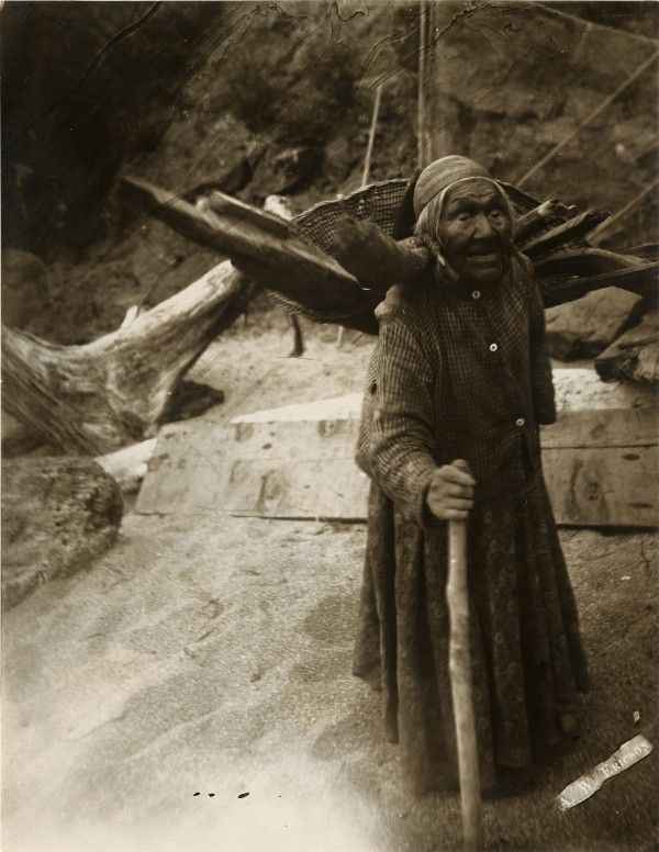 Photo of Photograph of an Indian woman standing with a burden basket full of wood on her back and steadying herself with a walking stick | Picture This