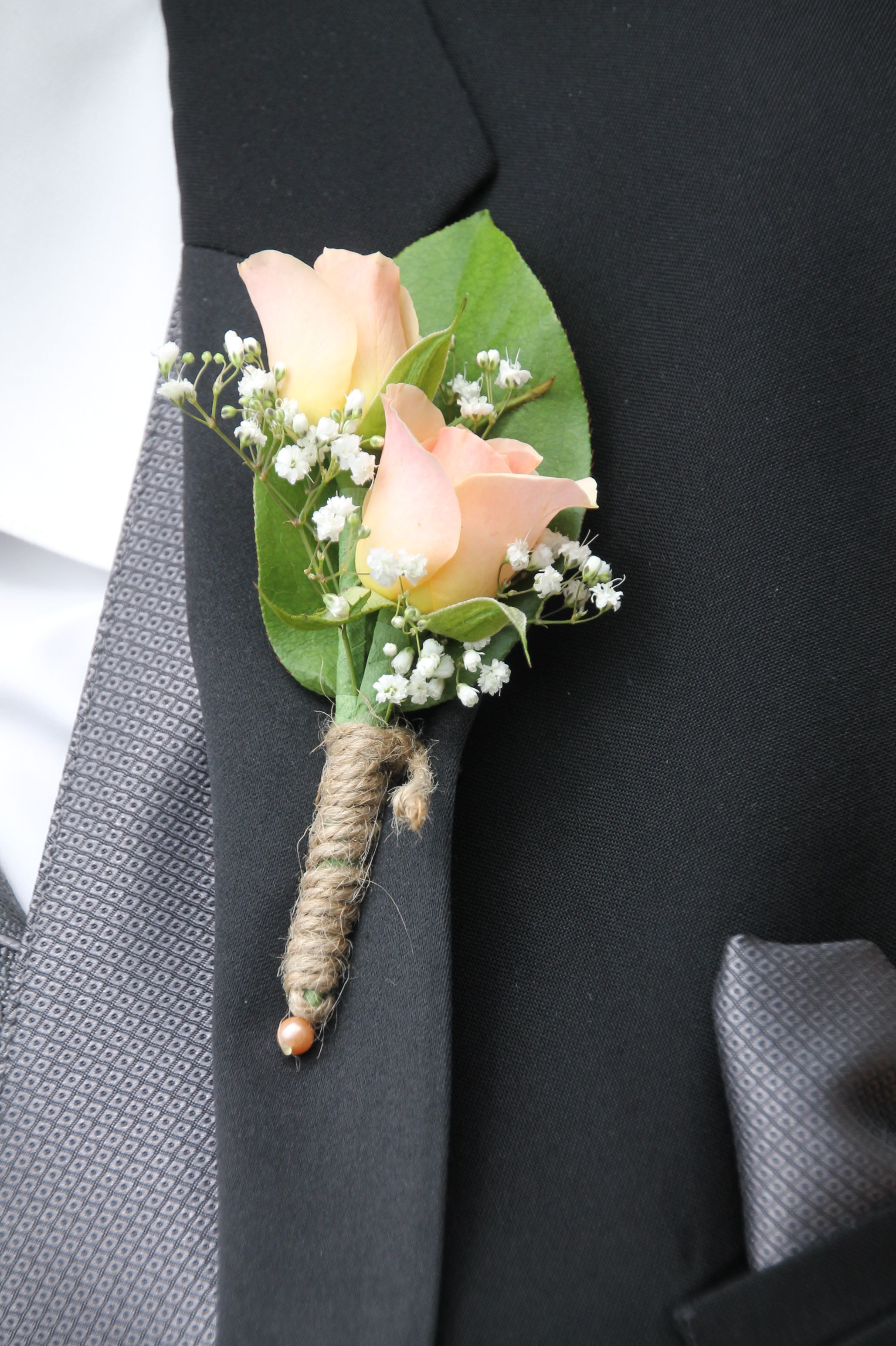 Peach Garden Rose Boutonniere boutonniere with peach/coral garden roses, wrapped with twine to