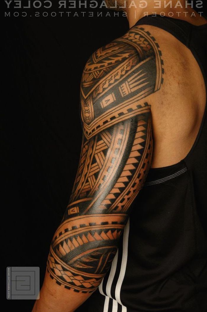 Cool Small Tattoos Large Tribal Arm Sleeve Tattoo Man Wearing A Black Top Standing In Front Of A Black Background